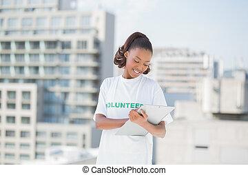 женщина, держа, доброволец, буфер обмена, улыбается, принятие, notes