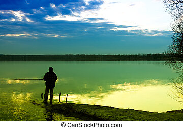 ловит рыбу, озеро