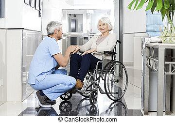 woman's, держа, рука, старшая, физиотерапевт, улыбается, wheelchai
